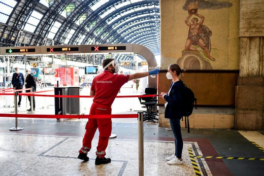 A passenger has her temperature taken to check for symptoms of COVID-19 before boarding a train to Milan's Central Station, Italy, Wednesday, June 3, 2020. A