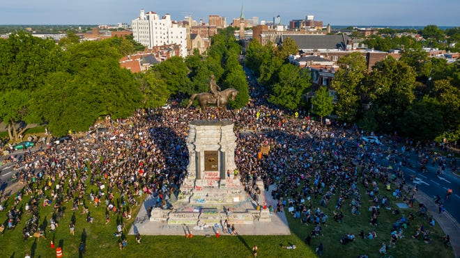 A large group of protesters gather around the statue of Confederate General Robert E. Lee on Monument Avenue near downtown in Richmond, Virginia on Tuesday, June 2, 2020.