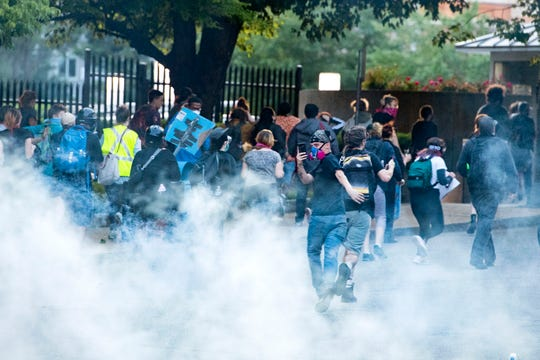 Protestors run up Otis Street as they are tear gassed from behind by members of the Asheville Police Department as they gathered for the fourth night in a row in downtown Asheville in response to the death of George Floyd at the hands of a Minneapolis police officer on June 3, 2020.