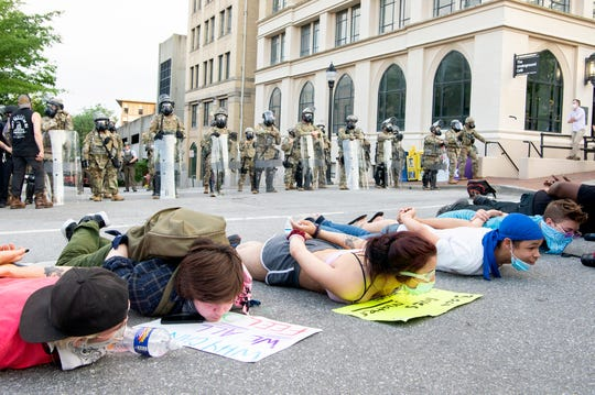 Protesters lay on the ground in front of the National Guard on June 3, 2020, as they gather for the fourth night in a row in downtown Asheville in response to the death of George Floyd at the hands of a Minneapolis police officer.