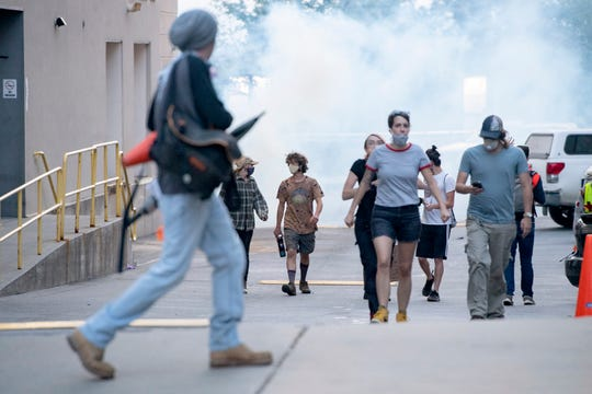 Protestors looks for a place to escape tear gas after curfew as they gathered for the fourth night in a row in downtown Asheville in response to the death of George Floyd at the hands of a Minneapolis police officer on June 3, 2020.