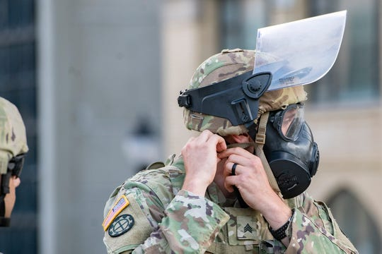 A member of the National Guard secures his gas mask as the 8 p.m. curfew hits and protestors gathered for the fourth night in a row in downtown Asheville in response to the death of George Floyd at the hands of a Minneapolis police officer on June 3, 2020.