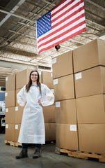 Allie Durr, an employee of Fletcher-based Diamond Brand Gear, models one of the gowns the company made for health care workers during the height of personal protective gear shortage in Western North Carolina.