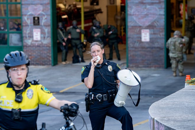 An Asheville Police officer announces the 8 p.m. curfew and asks protestors to disperse as they gathered for the fourth night in a row in downtown Asheville in response to the death of George Floyd at the hands of a Minneapolis police officer on June 3, 2020.