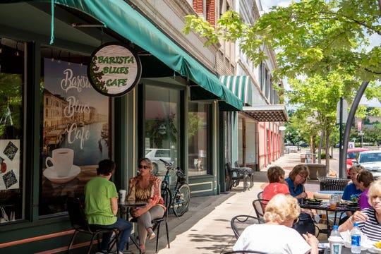 Women eat lunch and have coffee together outside of Barista Blues Cafe on Thursday, June 4, 2020 in Battle Creek, Mich.