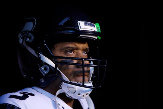 """In this Jan. 5, 2020, file photo, Seattle Seahawks' Russell Wilson waits to run onto the field for the team's NFL wild-card playoff football game against the Philadelphia Eagles in Philadelphia. Speaking to the media for the first time since the end of last season, Wilson didn't care to talk about the game that's helped make him famous. """"To be honest with you, I don't even want to talk about football right now,"""" Wilson said during a video conference Wednesday, June 3. """"I can't compare football to life and what the black community is going through right now"""" he said."""