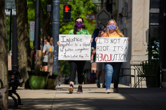 Anna Aardal, 21, of Howell, left and her sister Lily Aardal, 16, march with their signs through downtown Howell towards the historic courthouse in downtown Howell, Michigan as a small group of people protesting against police brutality and racism did come out to hold signs and rally June 4, 2020.