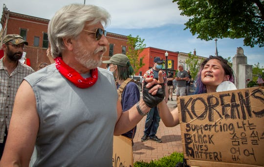 Anna Johnson, of Howell, right, reacts to a man who walks along the line of protesters with a raised middle finger as they hold their signs up in front of the historic courthouse in downtown Howell, Michigan as a large crowd came out June 4, 2020, to protest against police brutality and racism did come out to hold signs and rally.