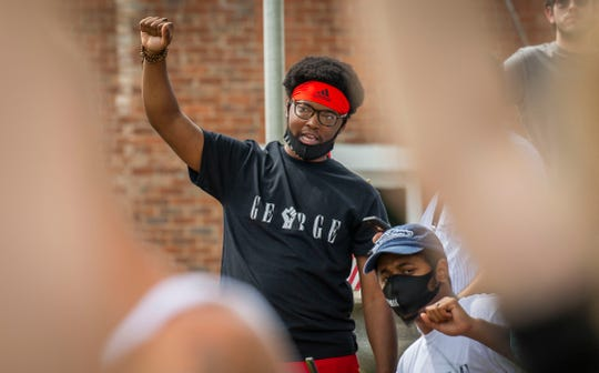 Andre Buford, 30, left and Joshua Sylvester, 24, both of Novi, participate in a 9-minute moment of silence with protesters in front of the historic courthouse in downtown Howell, Michigan as several people came out June 4, 2020, to protest against police brutality and racism did come out to hold signs and rally.