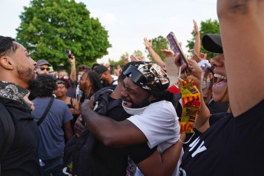 Protesters celebrate the end of a curfew called while marching through Detroit on the sixth day of protests against police brutality on Wednesday, June 3, 2020.