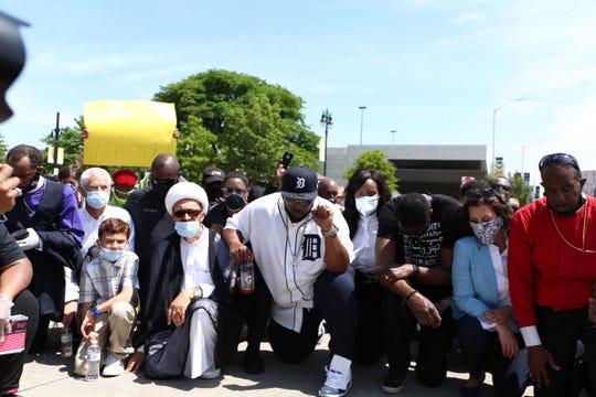 Hundreds of demonstrators and religious leaders across the state of Michigan kneel together to honor George Floyd in Detroit on Thursday, June 4, 2020.