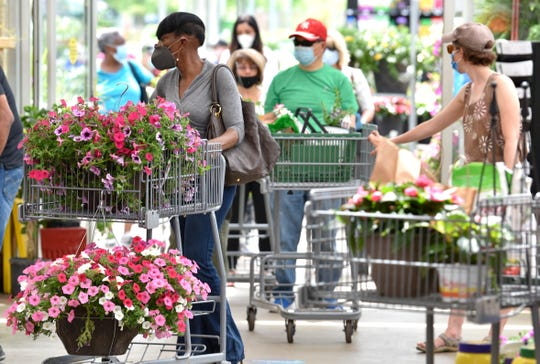 Detroiter Deborah Coklow, left, waits to pay for her hanging flower baskets at English Gardens.