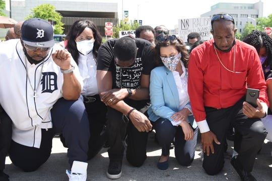 Gov.Gretchen Whitmer, center, prays with clergy including Bishop Charles Ellis of Greater Grace Church, right, on the corner of Woodward and Warren during a rally in honor of George Floyd, Thursday, June 4, 2020.