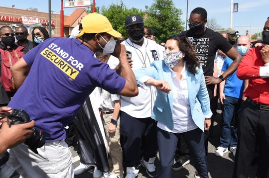 Gov. Gretchen Whitmer elbow bumps with Marlo Franklin of SEIU before the start of a rally in Highland Park in honor of George Floyd on Thursday, June 4, 2020.