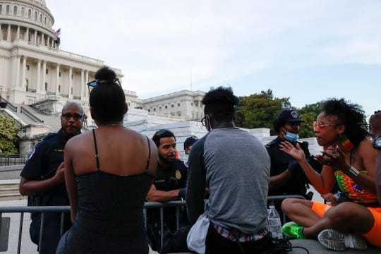 U.S. Capitol police officers talk with demonstrators as they have a conversation about racism in America as they protest the death of George Floyd, Wednesday on Capitol Hill in Washington.