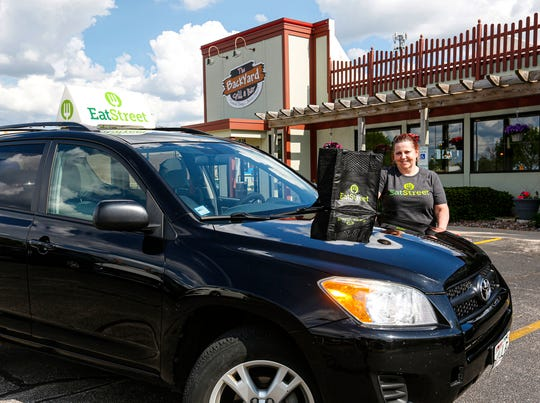 Dorothy Nagel, of Fond du Lac, poses for a photo with her EatStreet delivery vehicle May 27, 2020 outside Backyard Grill and Bar in Fond du Lac, Wis.
