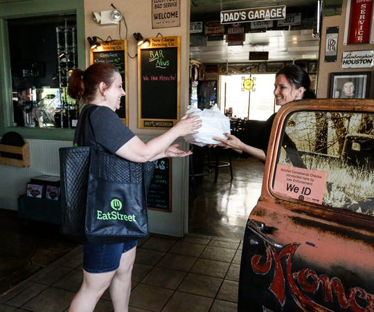 Dorothy Nagel, of Fond du Lac, picks up an EatStreet delivery from Jodi Roffers on May 27, 2020, at Backyard Grill and Bar in Fond du Lac, Wis.