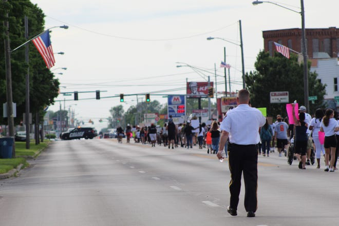 Fremont Police Chief Dean Bliss walks with protesters Wednesday during an anti-racism vigil on W. State Street.