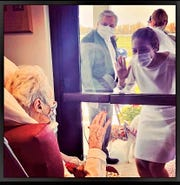 Waving to Grandma Dorothy Kurtz who is sitting inside the nursing home behind a glass door.  Minister Deb Lusher from Sandusky is pictured in the background.