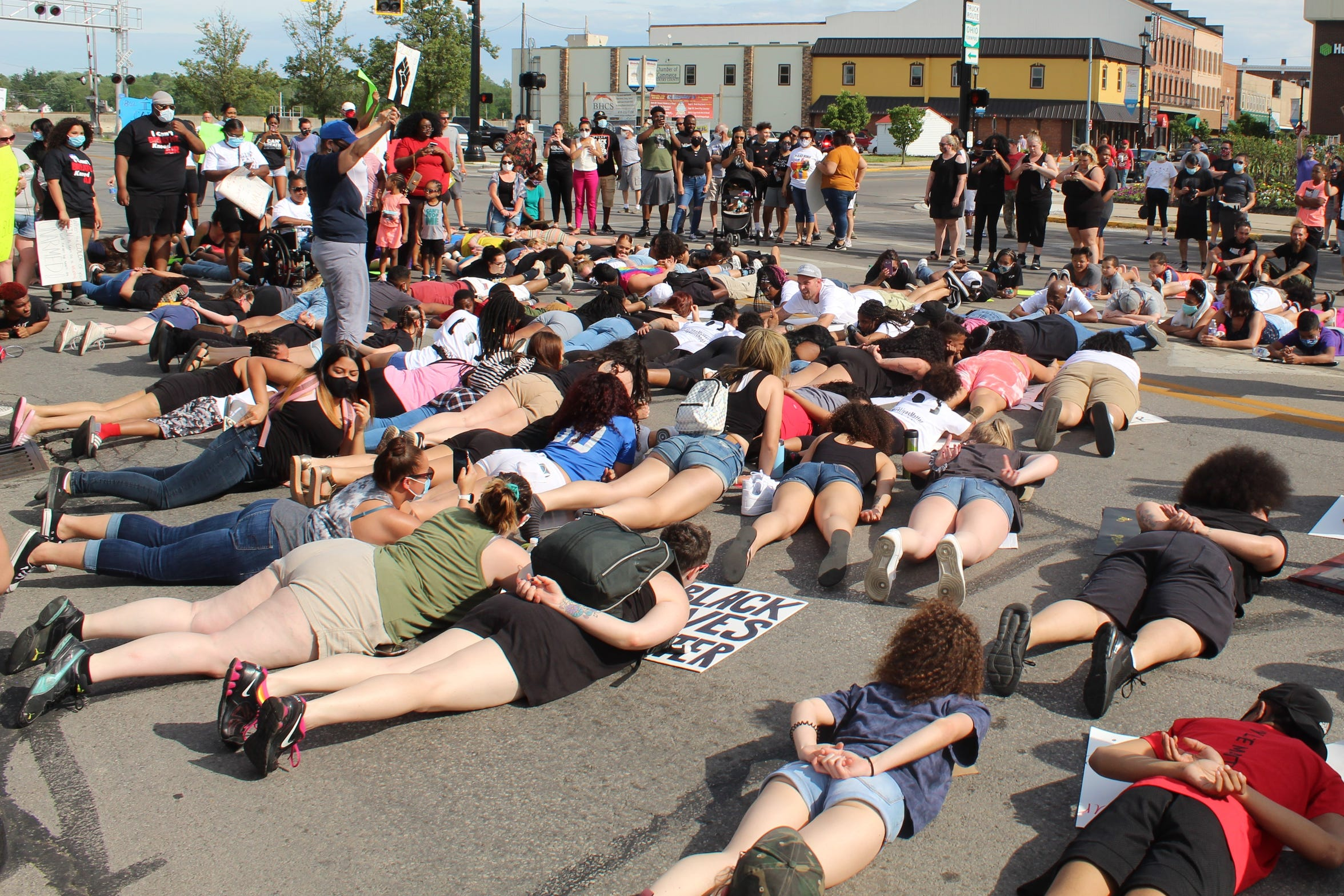 Dozens of residents lie down in protest near the intersection of Front and State Streets at an anti-racism vigil Wednesday evening in Fremont.