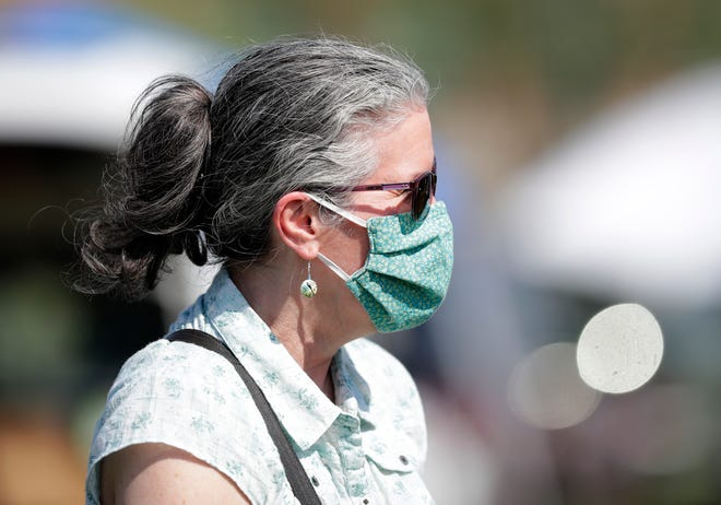 A woman wears a mask at Green Bay's first farmers market of the season on June 3, 2020. Due to coronavirus, the event has fewer vendors and was moved from Broadway to Leicht Memorial Park in downtown Green Bay for better social distancing.