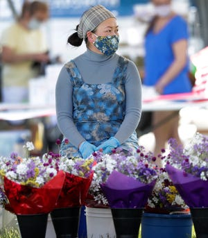 A vendor wearing a mask and gloves waits for customers at Green Bay's first farmers market of the season on June 3, 2020. Due to coronavirus, the event has fewer vendors and was moved to Leicht Park for better social distancing.