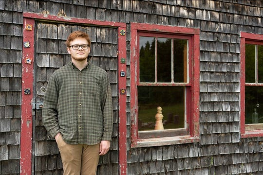 Norbert Blei Memorial Scholarship winner Solomon Lindenberg stands in front of Blei's famous chicken coop-turned-writing studio. Lindenburg plans to attend DePaul University in Chicago this fall to major in journalism.