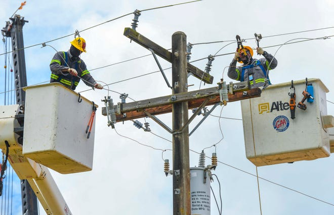 Guam Power Authority lineman apprentices Mike Francisco, left, and Kevin Castro, coordinate their efforts to install a primary line to power a new water reservoir atop Barrigada Heights in this June 4 file photo.
