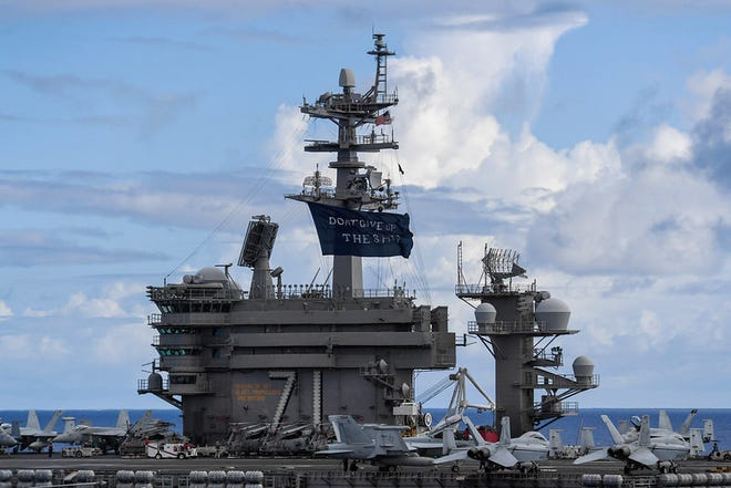 """USS Theodore Roosevelt (CVN 71) flies a replica of Capt. Oliver Hazard Perry's """"Don't Give Up the Ship"""" flag."""