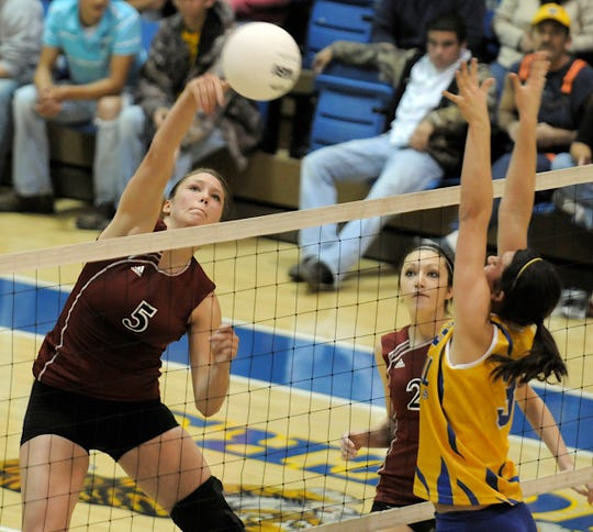 Henderson County's Jenna Hess (5) drives the spike past Caldwell County's Emily Meeks (3) during the 2008 regional championship game in Princeton.