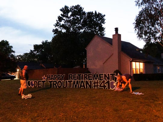 """As dusk sets in on a recent evening, Sign Gypsies Henderson owner Kerri Rowe (at right) and her fiancée, Bill Goodman, set up a """"Happy Retirement"""" yard greeting for Detective Shannon Troutman, who was preparing to retire from the Henderson Police Department. Most of their yard displays are set up at night in hopes of surprising the recipient."""