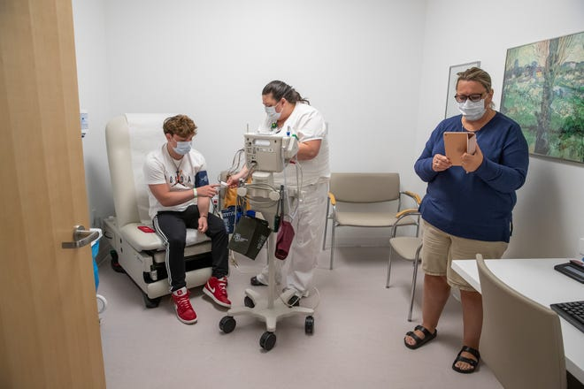 After receiving radiation, Chase Smith has his vitals taken inside Cleveland Clinic Taussig Cancer Center as his mother Kelli connects to a video call with Chase's wife Sadie and his father Brad on Monday, June 1, 2020. Due to COVID-19 restrictions, only one guest is able to accompany Chase to his appointment.