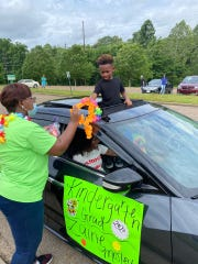 Isaac Lane Elementary kindergarten graduate Zaine Mosley stands through his car's sunroof for his drive-thru graduation at the end of May.