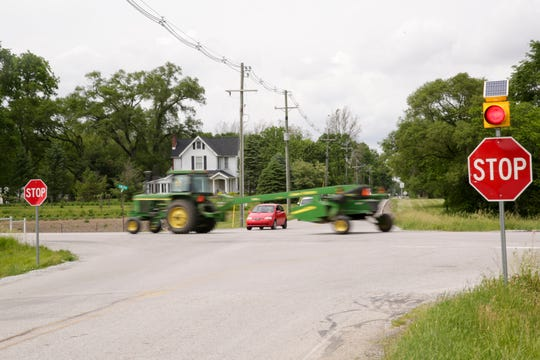 A tractor drives along Indiana 26 as a car waits to cross on Tippecanoe County Road 900 East, Thursday, June 4, 2020 in Lafayette.