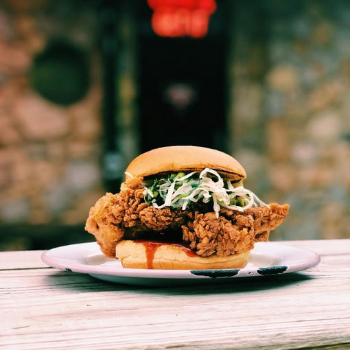 Spoonbill Watering Hole & Restaurant:Spoonbill's Chicken Sandwich - Fried Tabasco brined chicken on a Martin's potato roll with green onion and cilantro slaw and Tabasco Sweet and Spicy sauce.