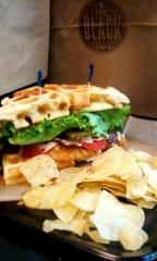 Black Cafe:Fightin'ville Fried Chicken Sandwich - a marinaded crispy fried chicken breast with lettuce, tomato, bacon and honey mustard served on a house made waffle with maple syrup for dipping.
