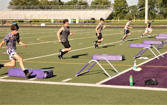 Bloom-Carroll High School football players take part in a workout earlier this week. Players had to go in shifts on the field and in the weight room to take persuasions because of the cornavirus pandemic. It is the first time athletes have been able to use school facilities since March 17.