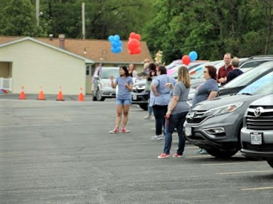 """Teachers and staff of Fairfield Christian Academy gather in the school's parking lot as the class of 2020 prepare to drive through for the """"Senior Clap Out,"""" celebrating what would have been seniors' last day of school, if schools hadn't been closed due to the coronavirus pandemic."""