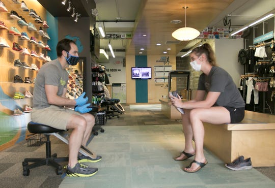 Running Lab sales associate Keith McCaffery asks questions to customer Ann Marie Plautz of Brighton about her running style at the downtown Brighton store Wednesday, June 3, 2020.