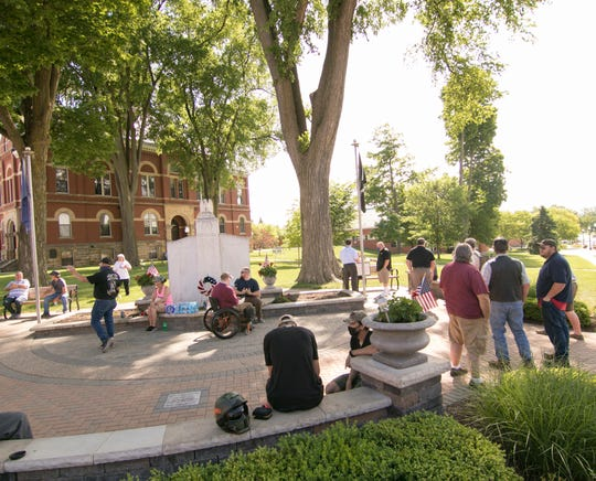 A small crowd gathers on the front lawn of the historic Livingston County Courthouse surrounding the Veterans Memorial in a support rally Thursday, June 4, 2020.
