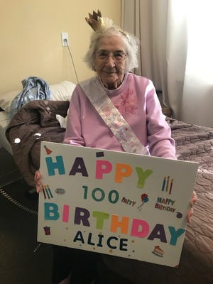 Alice Stoecker poses for a picture in her room at Regency at Lansing West in Delta Township. Stoecker turned 100 in May and celebrated with a socially distant, outdoor birthday party.