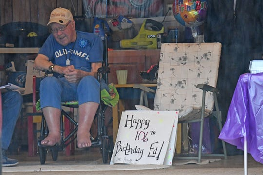 Ed Harpster enjoys a steady stream of friends in cars that passed by his garage in Lexington on Thursday to help him celebrate his 106th birthday.