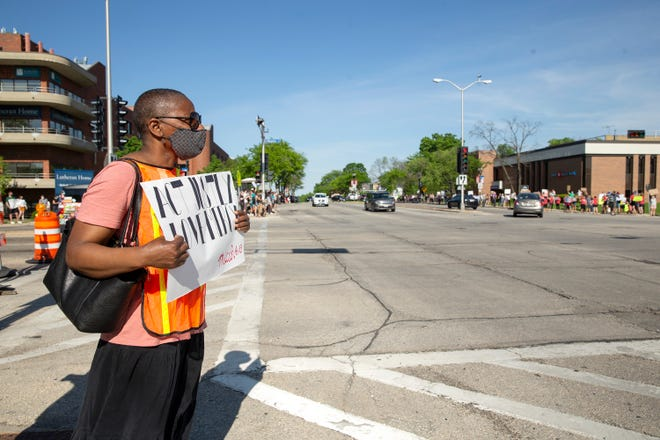 """Katherine Riebe holds a sign that read """"Act Justly Love Mercy"""" on North and Wauwatosa avenues this summer in Wauwatosa. Riebe is part of Tosa Together, a Wauwatosa group that aims to promote equity and inclusion in the city."""