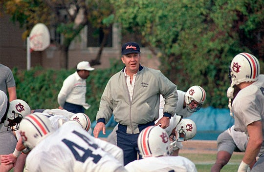 FILE - In this Dec. 27, 1988, file photo, Auburn NCAA college football coach Pat Dye walks through his players as they begin workouts in preparation for the Sugar Bowl in New Orleans. Former Auburn coach Pat Dye, who took over a downtrodden football program in 1981 and turned it into a Southeastern Conference power, has died. He was 80. Lee County Coroner Bill Harris said Dye passed away Monday, June 1, 2020, at the Compassus Bethany House in Auburn, Ala.(AP Photo/Bill Haber, FIle)