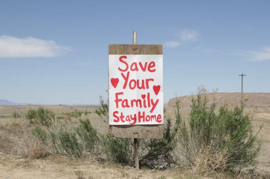 A homemade sign reminds motorists on Navajo Route 36 to follow the stay at home order by the Navajo Department of Health to combat the coronavirus. Navajo Nation President Jonathan Nez signed an executive order on June 3 to end the weekend lockdown for residents on the reservation.