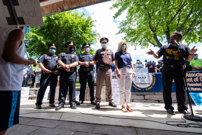 Port Huron Mayor Pauline Repp, second from right, St. Clair County Sheriff Tim Donnellon, center, and other area police chiefs stand next to local pastor Tray Smith as he addresses a crowd before a march through downtown Port Huron Thursday, June 4, 2020, in a march organized by the Port Huron chapter of the NAACP in response to social injustice. The march comes after more than a week of nationwide protests in response to the killing of George Floyd in Minneapolis.