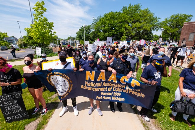 A group of people march through downtown Port Huron Thursday, June 4, 2020, in a march organized by the Port Huron chapter of the NAACP in response to social injustice. The march comes after more than a week of nationwide protests in response to the killing of George Floyd in Minneapolis.
