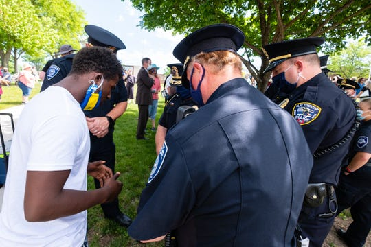 Lavaughn Price, left, youth president for the Port Huron chapter of the NAACP, joins several officers from Port Huron Police in a prayer before a march through downtown Port Huron Thursday, June 4, 2020, in a march organized by the Port Huron chapter of the NAACP in response to social injustice.