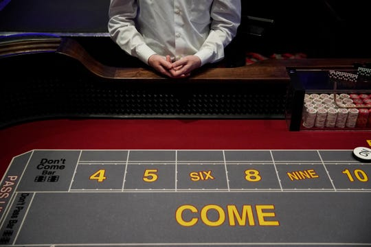 A craps dealer waits for customers before the Las Vegas hotel and casino reopens on Wednesday, June 3, 2020, in Las Vegas. Casinos were allowed to reopen early Thursday after temporary closings as a precaution against coronavirus. (Photo AP / John Locher)