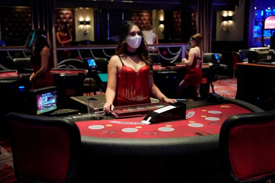 A dealer wearing a protective face mask waits for customers before the reopening of the D Las Vegas hotel and casino, June 3. Casinos and other businesses are navigating best practices to protect employees and customers from the spread of the coronavirus.